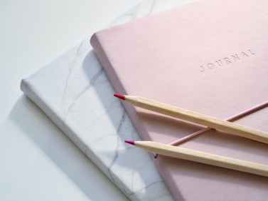 closeup photo of journal book and pencils
